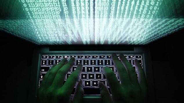 Un homme tape sur un clavier d'ordinateur.