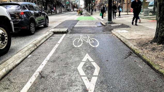 Une piste cyclable vide située sur le bord d'une rue de Vancouver.