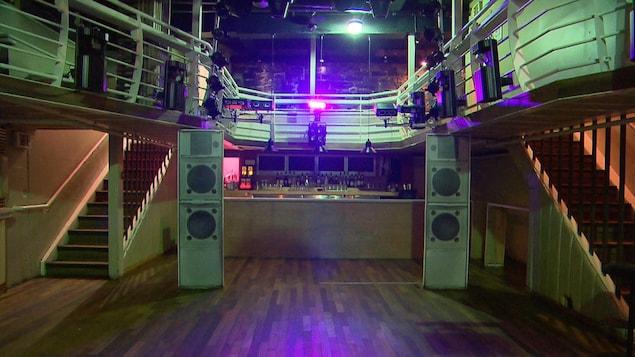 Un bar en arrière-plan avec des caisses de son, et un placher de danse