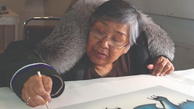 Pitaloosie Saila, en manteau, dessinant au crayon.