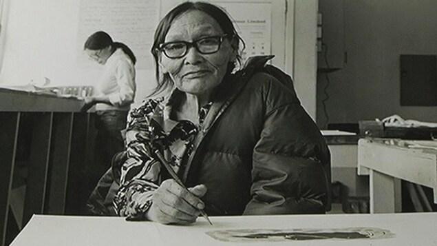 Une femme inuite, vêtue d'un manteau, semble prendre une pause de son dessin le temps que le photographe prenne la photo. Elle porte des lunettes à forte monture et tient un crayon en main.