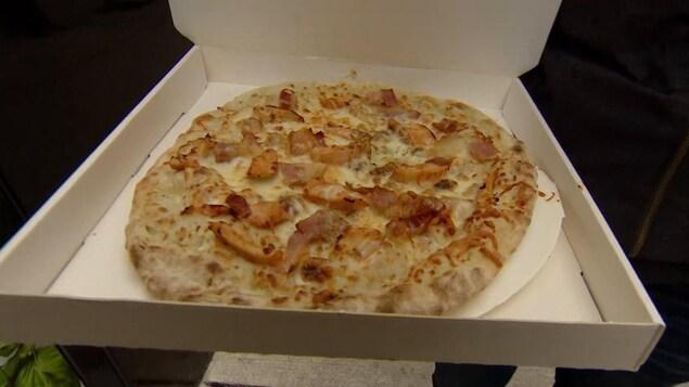 Une pizza dans une boite en carton.