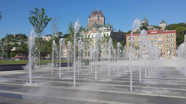 Des jets d'eau qui sortent de terre, avec le Château Frontenac en arrière plan