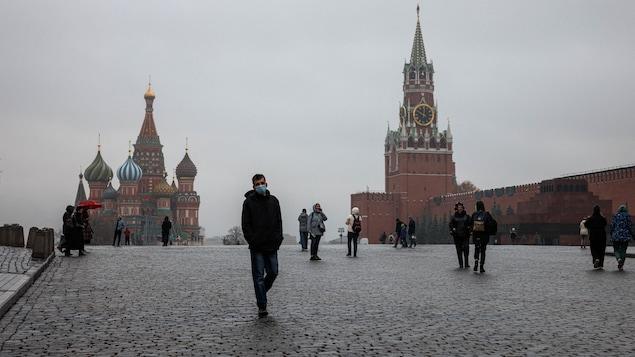 Un homme masqué marche sur la place Rouge. L'endroit est clairsemé.