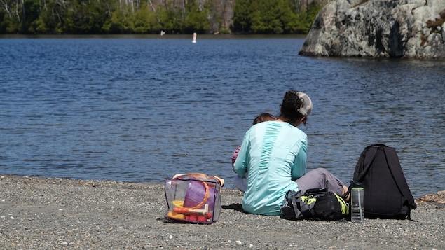 Une mère et sa filles assises sur une plage rocailleuse près d'un lac.
