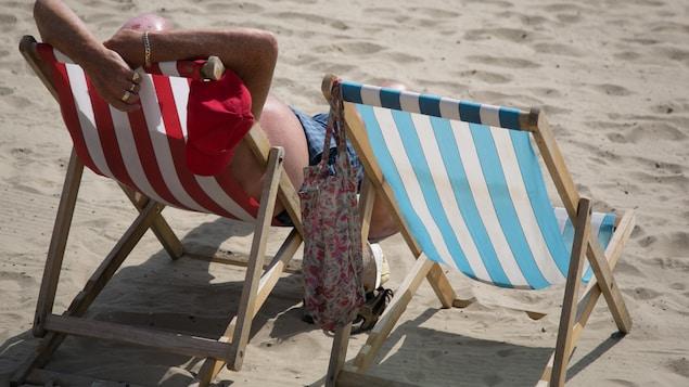 Un homme se fait bronzer sur une chaise sur une plage.