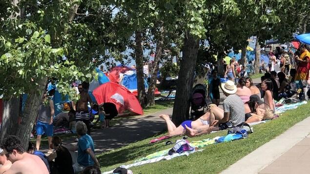 Des tentes et beaucoup de gens sur le bord de l'eau.