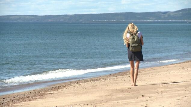 Une touriste marche sur la plage.