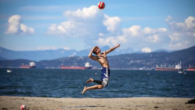 Un homme s'amuse sur la plage Kitsilano, à Vancouver, qui saute en frappant un ballon de volleyball.