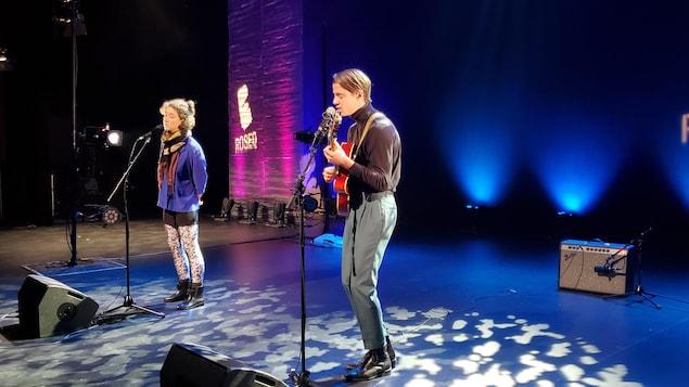 Deux artistes chantent sur scène.