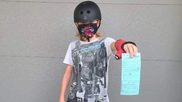 Un jeune homme, portant un masque, avec un casque et une planche à roulette dans une main, tend un papier d'une autre main.