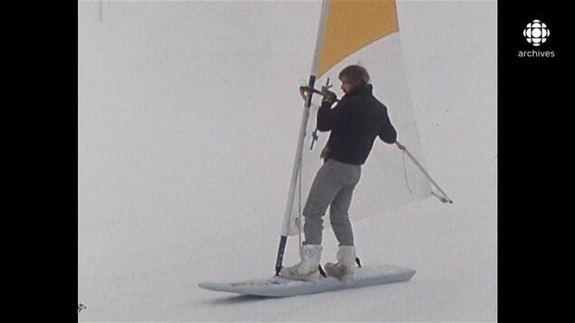 Homme glissant sur une planche à voile sur neige sur une surface glacée et légèrement enneigée