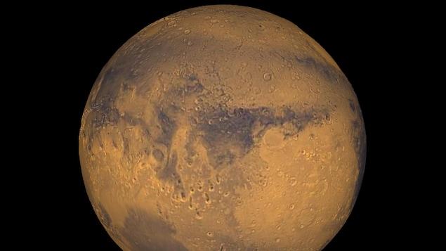 Une sphère, qui est rouge et orange et qui a une multitude de trous, est vue dans un espace tout noir.