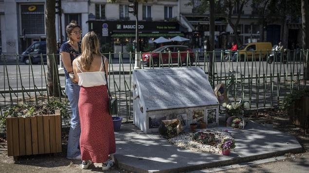 Deux femmes, près d'une plaque commémorative.