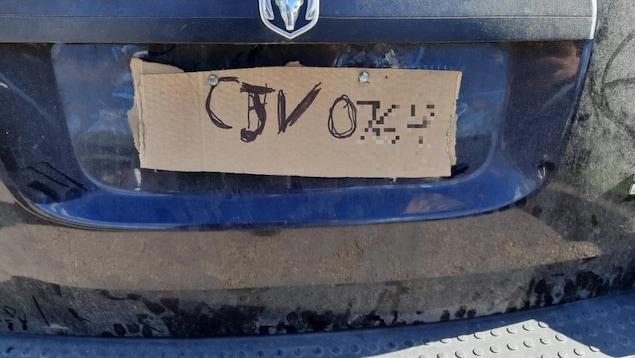 Un bout de carton gribouillé sur une voiture