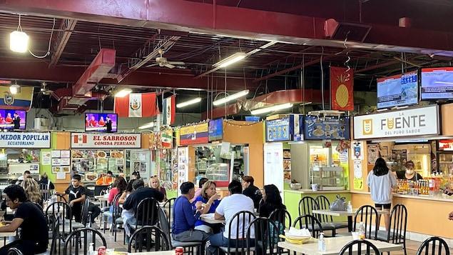 Plusieurs personnes sont attablées pour manger et discuter à la Plaza Latina de Toronto. Autour de l'aire de restauration, on trouve des comptoirs et petits commerces avec des affiches en espagnol.