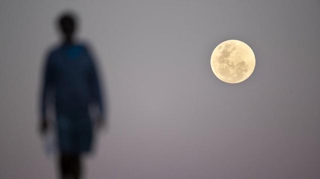 Un rond lumineux, la Lune, est photographié dans le ciel. La silhouette d'une personne est vue à gauche de l'astre.