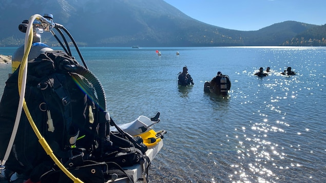 Une veste de plongée est posée sur une table et au loin, dans le lac, cinq plongeurs sont dans l'eau.