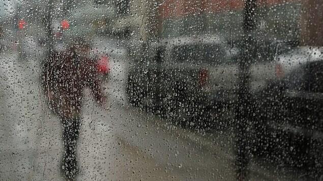 Une vitre remplie de pluie avec un individu qui marche dans une rue.