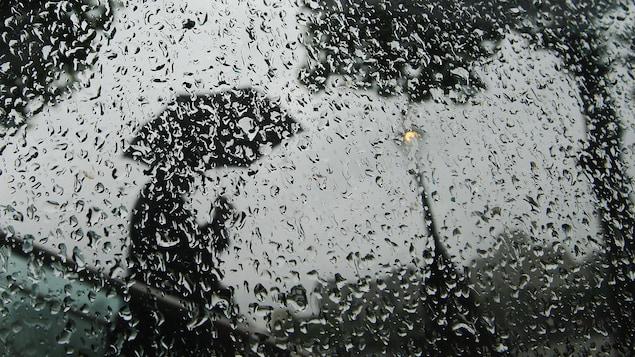 Un homme marche avec un parapluie derrière une vitre couverte de gouttes d'eau.