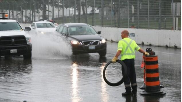 Un employé municipal se tient sur le boulevard Lakeshore Ouest inondée pour barrer la route.