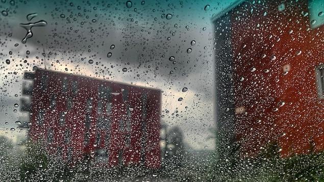Des gouttes de pluie glissent sur une vitrine.
