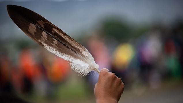 Una mano sostiene una pluma de águila.