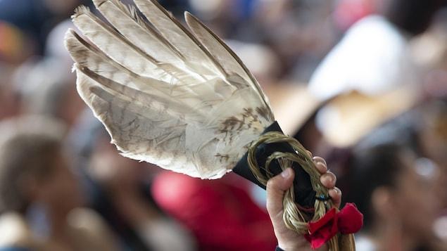 Une femme tient une plume d'aigle avec un ruban rouge pendant les cérémonies marquant le dépôt du rapport de l'ENFFADA à Gatineau, le 3 juin 2019.