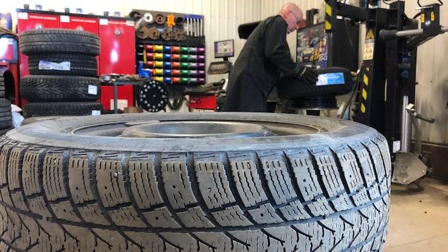 Un garagiste travaille sur des pneus.