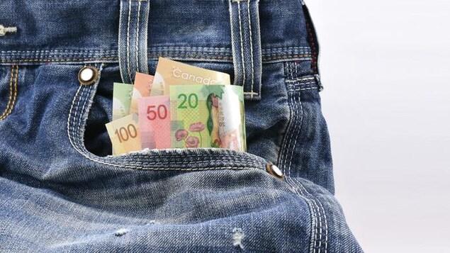 Des billets de 20, 50 et 100 dollars dans la poche d'un pantalon.