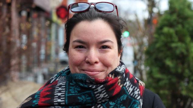 La poète multidisciplinaire innue Natasha Kanapé Fontaine pose dans la rue avec un foulard coloré.
