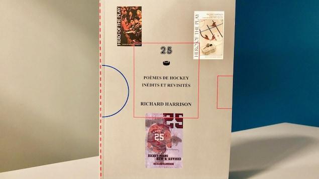 Le recueil 25-Poèmes de hockey, inédits et revisités, posé debout sur une table devant un fond bleu et gris.