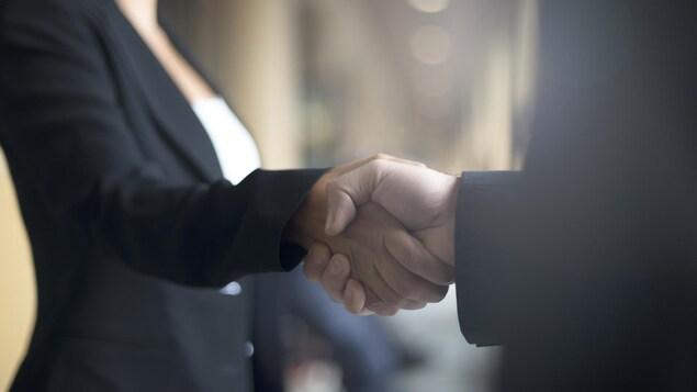 Une femme et un homme en train de se serrer la main. On ne voit pas leurs visages.