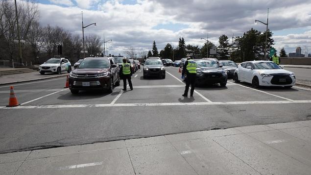 Des polciiers près d'une file de voitures sur un pont.