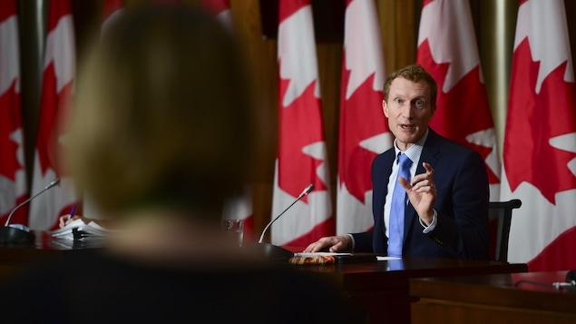 Marc Miller en point de presse devant des drapeaux du Canada.