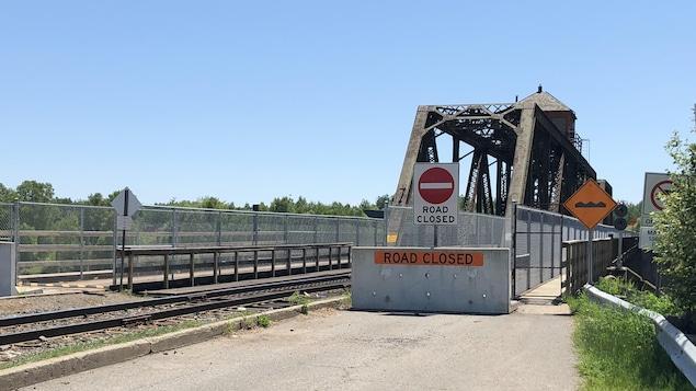 Un pont ferroviaire avec un muret de béton et un panneau indiquant que la route est fermée.
