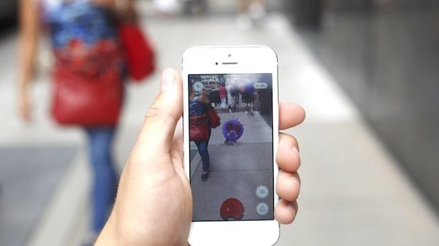 Un Pokémon apparaît sur le téléphone d'un joueur de Pokémon Go dans une rue de Toronto.