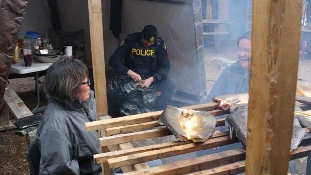 Des femmes discutent devant du poisson en train de fumer avec un policier derrière.