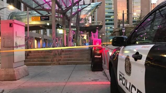Une voiture de police devant une station de train fermée.
