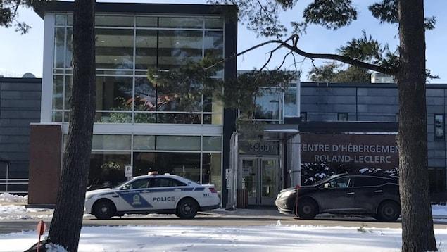 Une voiture de police devant un bâtiment avec l'inscription «Centre d'hébergement Roland-Leclerc».