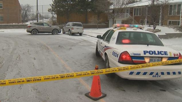 Photo d'une voiture de police et d'une bande jaune bloquant la circulation près de l'école.