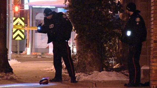 Des policiers regardent le sol avec la lumière de leur lampe torche.