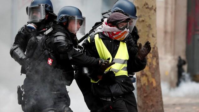 Des policiers retiennent un manifestant.