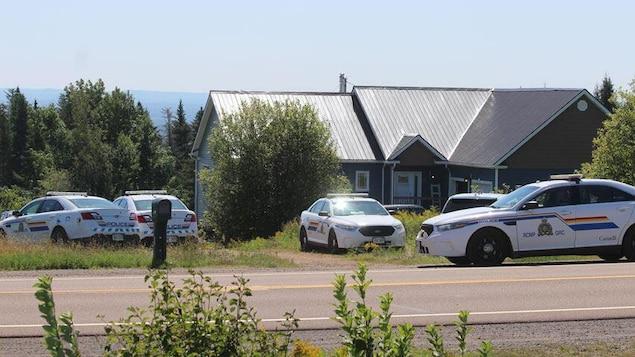Quatre voitures de la GRC stationnées tout autour d'une grande maison.