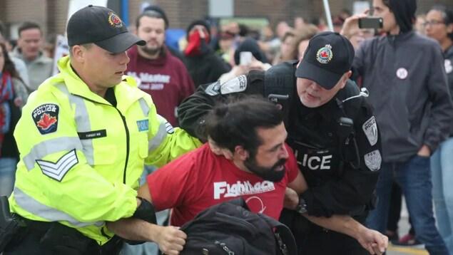 Deux policiers tiennent un manifestant.