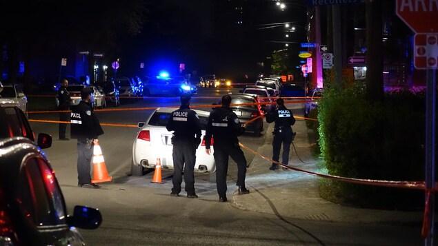 Des policiers entourent une voiture blanche.
