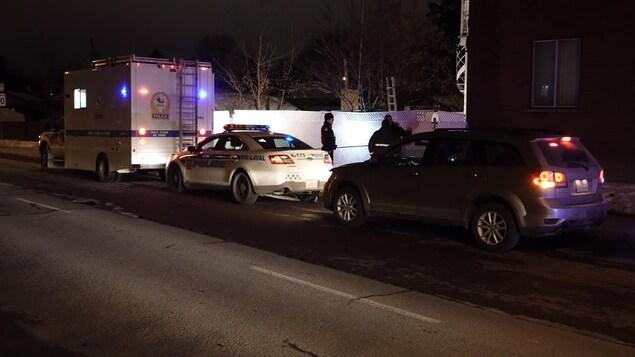 Deux voitures de police et des policiers se trouvent sur la scène de crime.