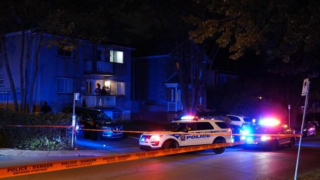 Des voitures de police sont garées devant le l'édifice où a eu lieu le drame.