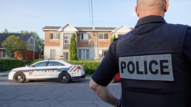 Un policier de dos se tient devant un immeuble.