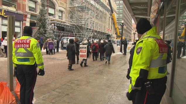 Des policiers d'Ottawa avec des vestes jaunes surveillent des manifestants pro-vie sur la rue Sparks, à Ottawa.